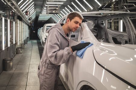 Employee car body painting shop checks the quality of the painted surface 版權商用圖片