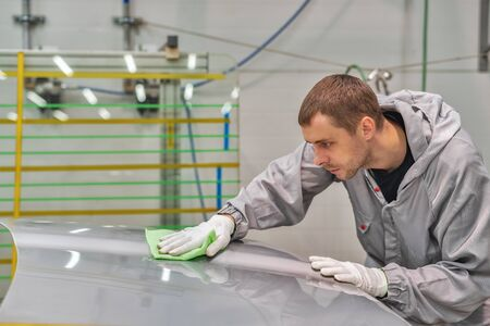 An employee of the paint shop of an automobile plant learns to remove dust with a special wax rag. Production interiors. Stock Photo