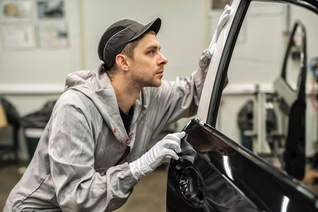 L'atelier de peinture de carrosserie des employés vérifie la qualité de la surface peinte Banque d'images