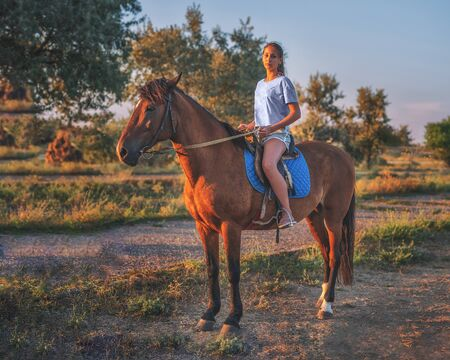 a young girl riding a horse in the evening light of the sunset. Natural light.