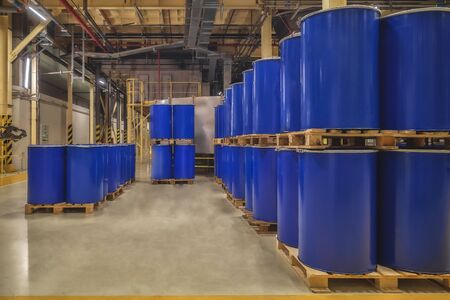Blue metal barrels. Chemical industry. Metal barrels for chemicals. Storage racks. Barrels are stored in a warehouse. Warehouse storage. Stock Photo