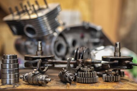 On the table are the engine parts of an old motorcycle. Restoring vintage motorcycles