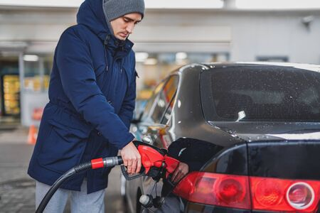 Close-up of a man pumping gasoline into a car at a gas station. Natural light. Stock Photo