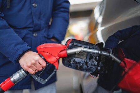 Close-up of a man pumping gasoline into a car at a gas station. Natural light.