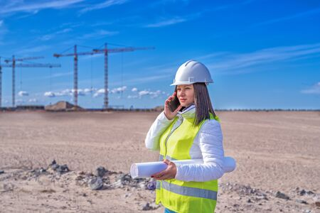 a female civil engineer in a white helmet is talking on the phone in the background of construction. natural light. Banco de Imagens