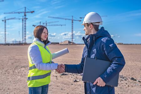 A Builder and a real estate agent shake hands in front of a building under construction. The handshake between the Builder and client
