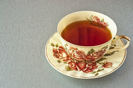 on the gray table is a beautiful Cup of tea on a saucer with a picture of roses. Natural light Stock Photo