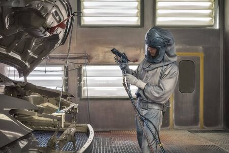 An employee of the paint shop of the automotive plant paints car elements. Production line.