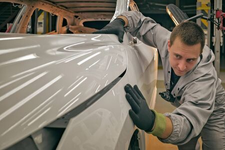 An employee of the quality department of the automobile plant checks the quality of the car body paint. Imagens