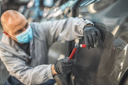 An employee of a car factory wearing a protective medical mask eliminates a small metal defect with a hand tool. Work during the pondemia.
