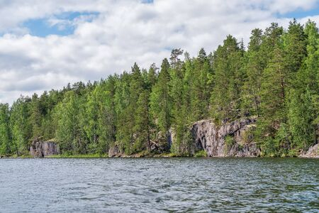 Forest lake with rocky shores bright day. Karelia.
