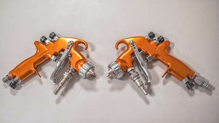 two orange professional sprayers on a grey background. Paint shop. Automobile plant.