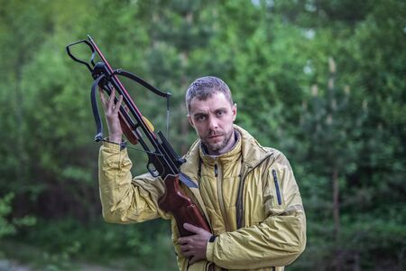 Young man shooting with a crossbow in a forest. A man with a crossbow in his hands. Imagens