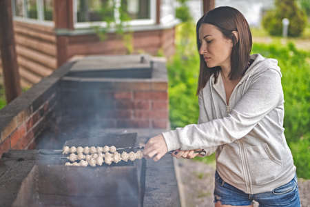 A woman prepares mushrooms on the grill. Vegetarianism.