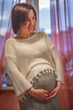 A pregnant woman with a smile on her face strokes her stomach. Natural light Imagens