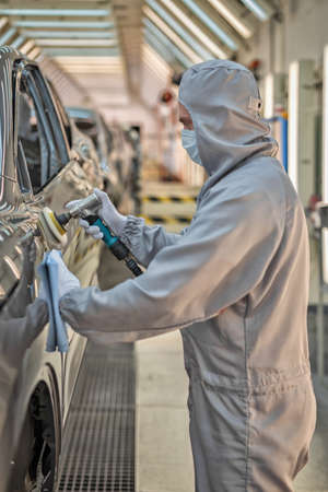 An employee of the car body paint shop in white gloves and a medical mask on his face polishes the painted surface. Work during the pandemic. Automobile plant