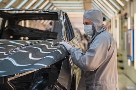 An employee of the car body paint shop in white gloves and a medical mask on his face checks the quality of the painted surface. Working during the pandemic
