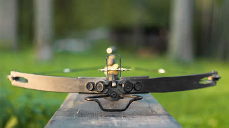 Loaded crossbow on a wooden bench. Selective focus, natural light