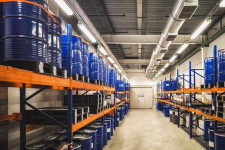 Blue metal barrels. Chemical industry. Metal barrels for chemicals. Storage racks. Barrels are stored in a warehouse. Warehouse storage.