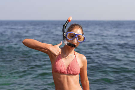 Happy girl in mask and snorkel on the beach in summer with sea background. Natural light