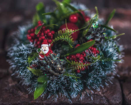 Christmas wreath on a brick wall background. Christmas decorations with Santa Claus figurine. Christmas decor. Close up