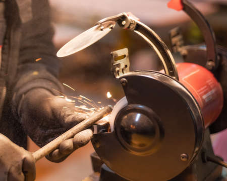 Close-up of the hands of a worker in black gloves working on a metal part on a red grinding machine