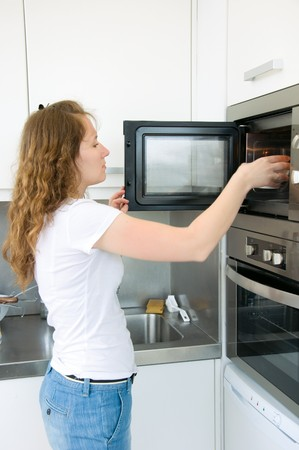 adorable woman is cooking by oven photo