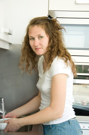 young woman is washing dishes photo