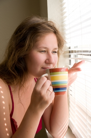 woman drinking coffee and looking through window photo