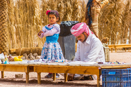 bedouin: Sharm El Sheikh, Egypt - May 07, 2014: Bedouin and his daughter keep souvenir shop in desert.
