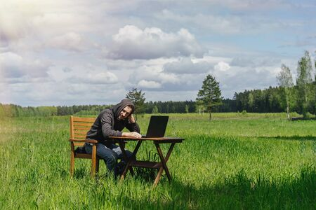 A man works at a table with a laptop in an empty field. Remote work in the field