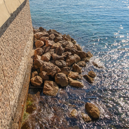 bordering: Waterfront with large stones bordering the Mediterranean Sea, a sunny day