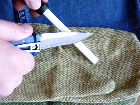 carbonaceous: Sharpening of a small penknife on a ceramic musat