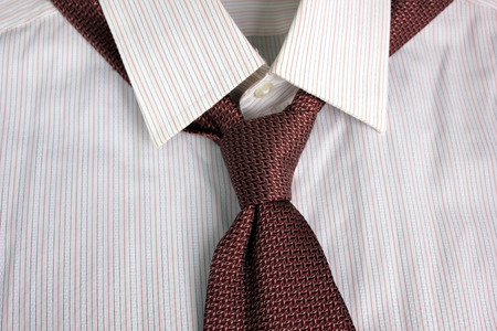 tied in: The tie tied in knot round a shirt collar