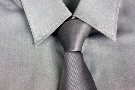 tied in: Gray tie tied in knot round a collar of a gray shirt Stock Photo