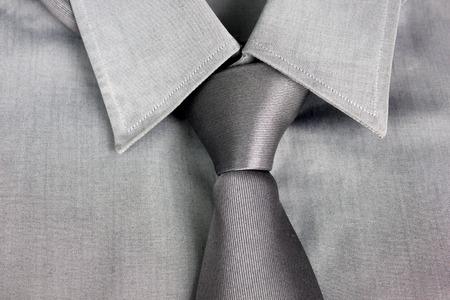lazo regalo: Lazo gris atado en el nudo alrededor de un cuello de una camisa gris