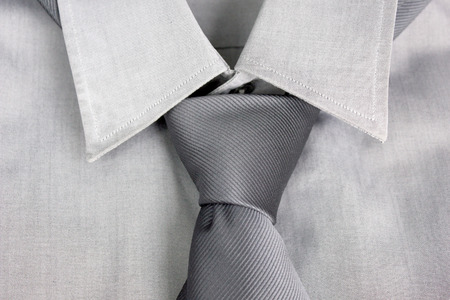 strip shirt: Gray tie tied in knot round a collar of a gray shirt Stock Photo