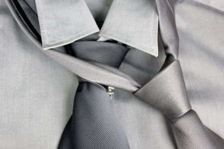 tied in: Two gray ties tied in knot round a collar of a gray shirt