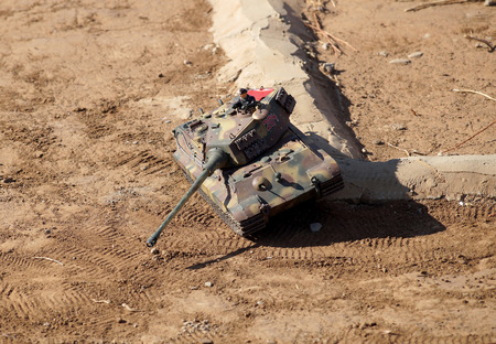 overcoming: Tank overcoming of obstacles in the toy ground Stock Photo