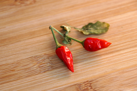 poignant: Scattering of burning small pepper on a chopping board