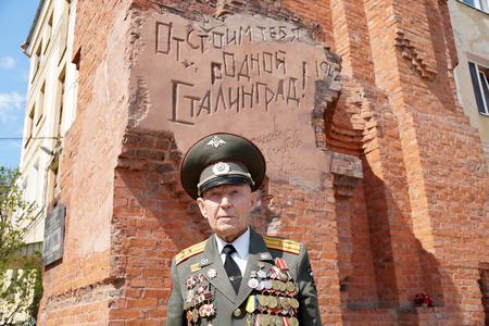 firmness: Defender of Stalingrad veteran of World War II colonel Vladimir Semenovich Turov against an inscription We will defend you native Stalingrad at Pavlovs House Stock Photo