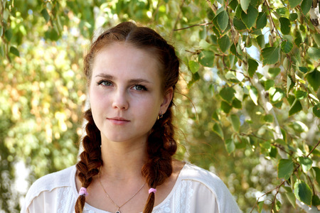 appearance: Beautiful girl of Slavic appearance against a birch