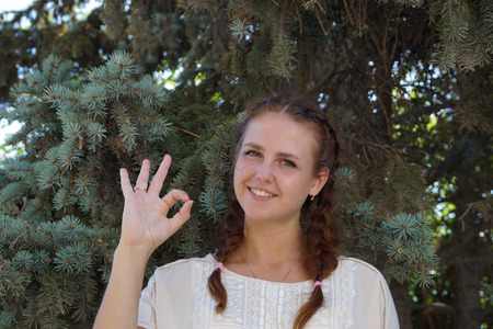 firtree: Girl of Slavic appearance against a fir-tree
