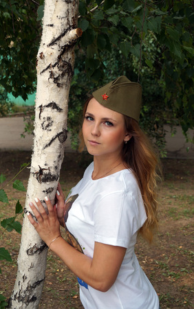 garrison: Girl in a military garrison cap and in a t-shirt about a birch