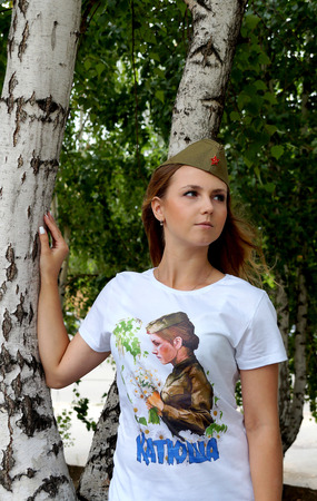 garrison: Girl in a military garrison cap and in a t-shirt with the name Katyusha about a birch