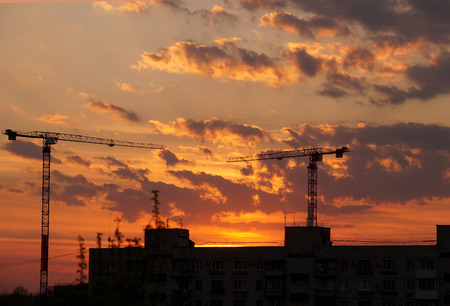 Evening city decline against construction cranes