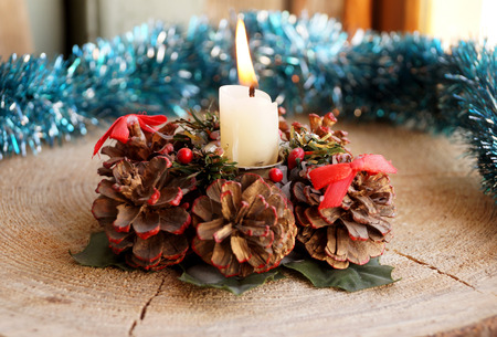 Wax candle on a decorative support from cones Stock Photo