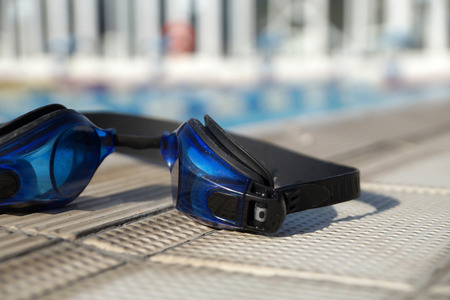 Blue goggles for swimming on a side of the swimming pool Stock Photo