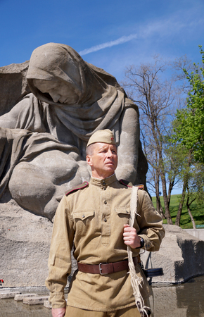 garrison: Fighter of Red Army in the form of times of World War II with the machine gun at a historical monument (fragment)