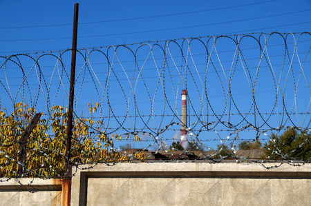 Barbed wire on the concrete fence protecting the industrial enterprise 免版税图像 - 80596763